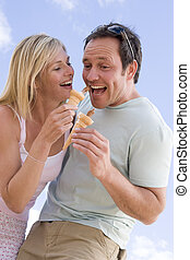 Couple outdoors eating ice cream and smiling