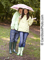Couple outdoors in rain with umbrella smiling
