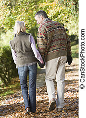 Couple outdoors walking on path in park holding hands and smiling (selective focus)