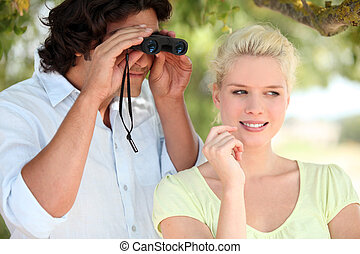 Couple outdoors with a pair of binoculars