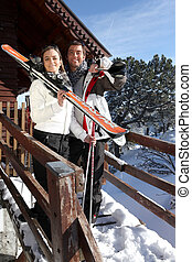 Couple outside a ski lodge