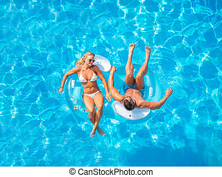 Couple Outside Relaxing In Swimming Pool