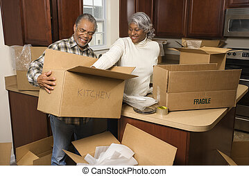 Middle-aged African-American couple packing moving boxes in kitchen.