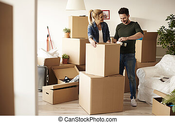 Couple packing stuff among plenty of cardboard boxes