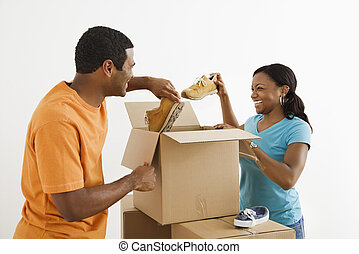 Couple packing together. - African American male and female...