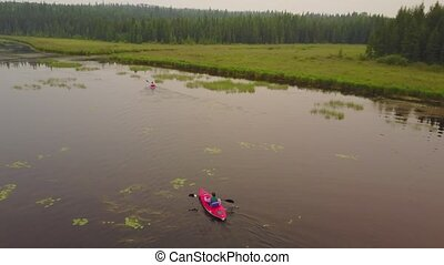 Couple paddling in kayaks enjoying a calm, misty lake. -...