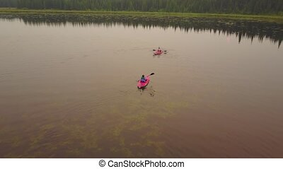 Couple paddling in kayaks enjoying a calm, misty lake.