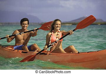 couple paddling their kayak in hawaii