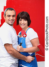 Couple painting a room bright red