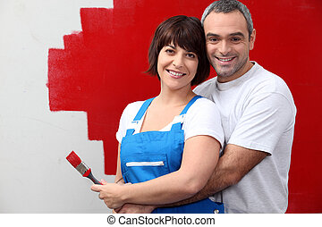 couple painting a wall in red