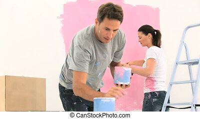 Couple painting a wall with the colour pink