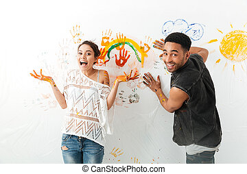 Couple painting on white wall by hands together