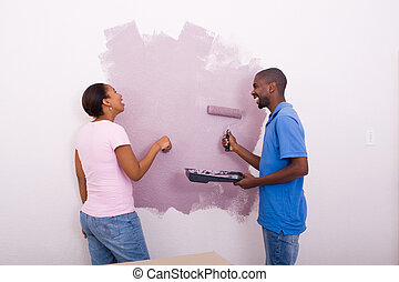 couple painting wall together