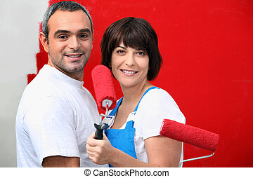 Couple painting wall with roller
