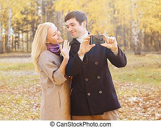 couple, parc, jeune, automne, smarphone, portrait, confection, sourire, selfie, heureux