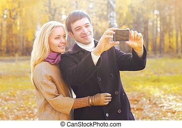 couple, parc, jeune, ensemble, automne, smarphone, portrait, confection, sourire, selfie, heureux