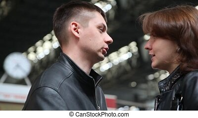 couple parting: talking, then kissing in night depot against...