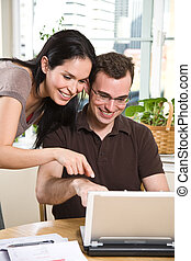 Couple paying bills by online banking - A happy couple...