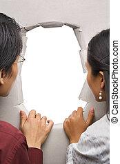 Couple peeking through hole in wall