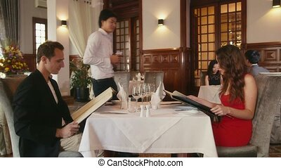 Couple, people dining at restaurant