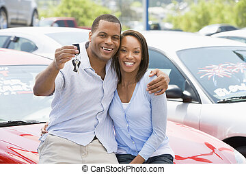 Couple picking up new car from lot