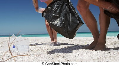 Couple picking up rubbish on the beach and putting it into ...