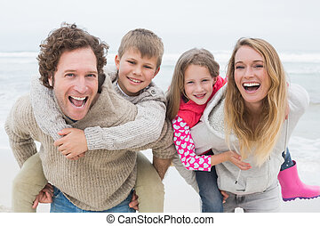 Couple piggybacking kids at the beach - Portrait of a happy...
