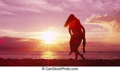 Couple piggybacking on beach having fun enjoying sunset on honeymoon summer travel vacation holiday. Happy joyful lovers playful together.