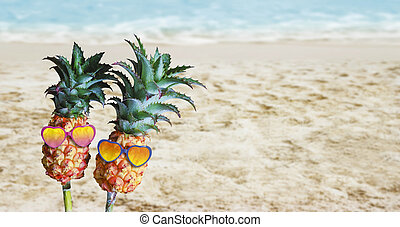 Couple pineapples with sunglasses on sand at the beach hello summer concept