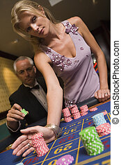 Couple placing bet at roulette table in casino
