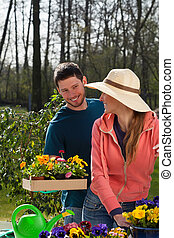 Couple planting flowers in garden