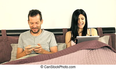 Couple play in bed with technology