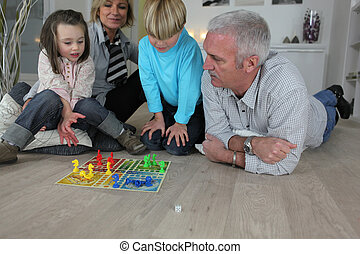 Couple playing a board game with their grandchildren