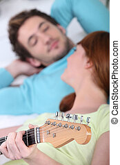 Couple playing a guitar at home