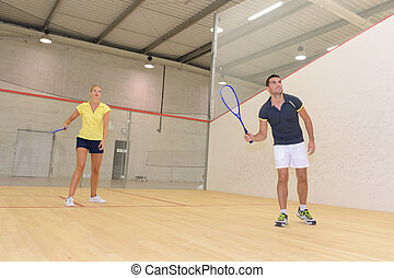 couple playing at an indoor tennis court