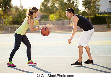 Couple playing basketball outdoors