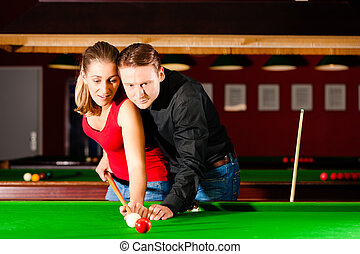 Couple playing billiards - Couple (man and woman) in a...