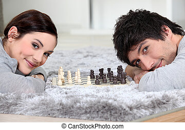 Couple playing chess in bed