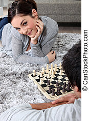 Couple playing chess on the floor