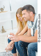 Couple playing computer game, woman losing
