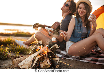 Couple playing guitar and frying marshmallows on bonfire -...