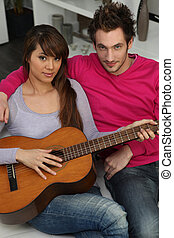 couple playing guitar at home