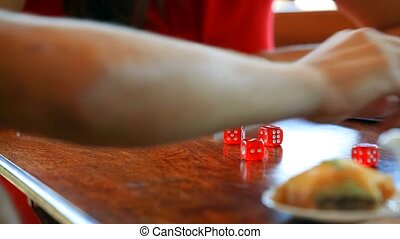 Couple playing in the dice and eat oriental sweets.
