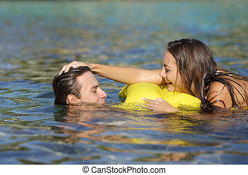 Couple playing on the beach in summer vacation