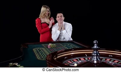 Couple playing roulette is eager to win at the gambling house. Black