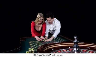 Couple playing roulette is eager to win. Black