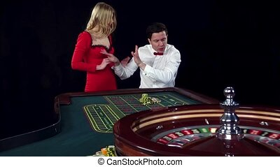 Couple playing roulette wins at the casino. Black - Couple...