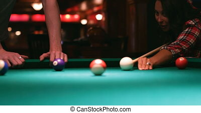 Young couple playing snooker in night club 4k