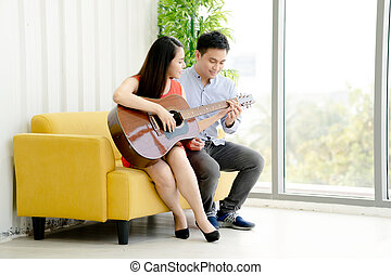 Couple playing the guitar at home