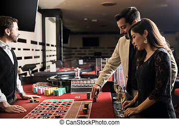Couple playing the roulette wheel